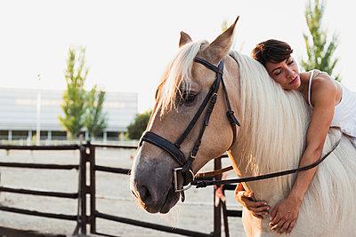 Portrait of woman relaxing on riding horse - p300m2042173 by Kike Arnaiz