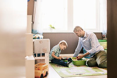 Father playing with son while sitting at home - p426m1179359 by Kentaroo Tryman