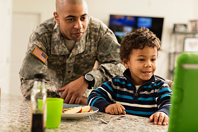 Mixed race soldier father and son eating in kitchen - p555m1412424 by Roberto Westbrook