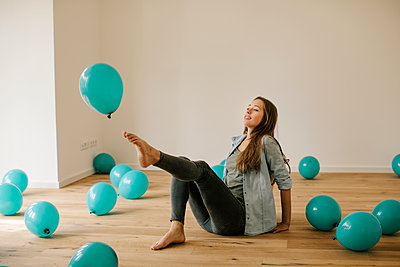 Young woman in new apartment playing with balloons - p586m1064885 by Kniel Synnatzschke