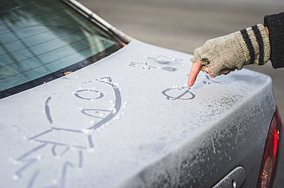 Person Drawing Pictures in Frost on Car - p694m1221867 by Eric Schwortz