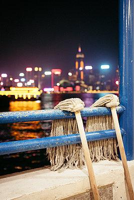 Zwei Wischmopps zum Trocknen auf dem Schiffsdeck vor Skyline Hongkongs - p795m2187812 von JanJasperKlein
