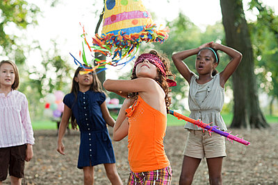 Girl at birthday party hitting pinata - p9245613f by Image Source