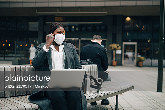 Businesswoman with laptop looking away while sitting on bench during pandemic - p426m2270317 by Maskot