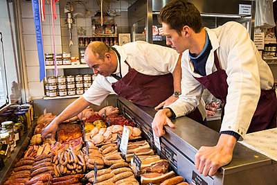 Two men wearing aprons standing at the counter of a butcher shop. - p1100m1575693 by Mint Images