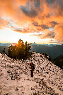 Man hiking on mountain ridge with sunset, scenic view behind. - p1166m2255904 by Cavan Images
