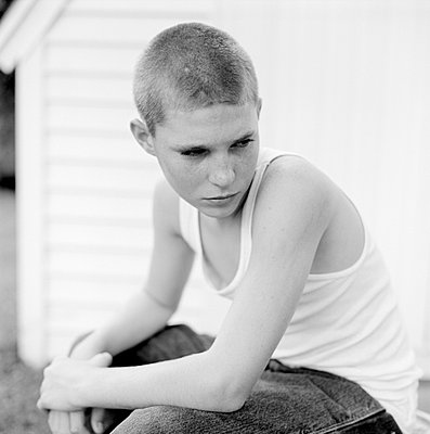 Young boy in tank top sitting outside - p3721328 by Dennis Slape