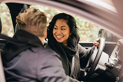 Smiling woman looking back while driving electric car - p426m2195229 by Maskot