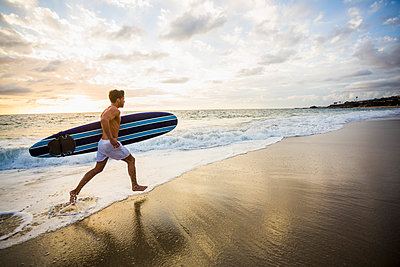 Caucasian surfer carrying board in waves - p555m1419627 by Mike Kemp