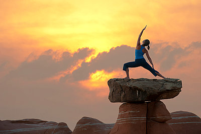 Caucasian woman practicing yoga on top of rock formation - p555m1478288 by Pete Saloutos