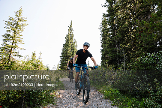 Man mountain biking on trail in woods - p1192m2129203 by Hero Images
