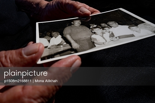 Wrinkled hands holding vintage photograph - p1508m2168811 by Mona Alikhah