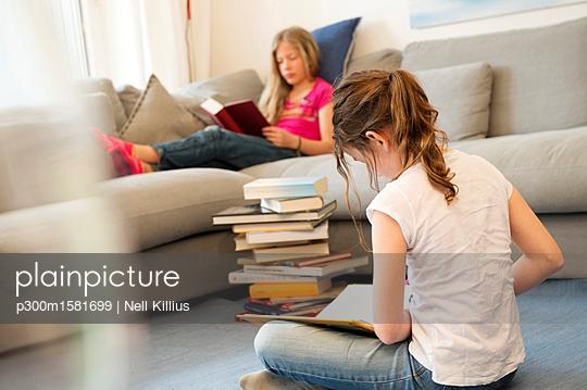 Two girls sitting in the living room reading books - p300m1581699 von Nell Killius