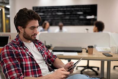 Bearded man using tablet in office - p1166m2234911 by Cavan Images