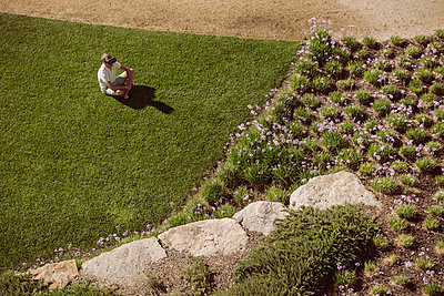 Man wearing VR glasses sitting on lawn in garden - p300m1536095 by Mareen Fischinger