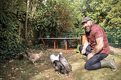 Man in his own garden, man feeding free range chickens - p300m2059307 by realitybites