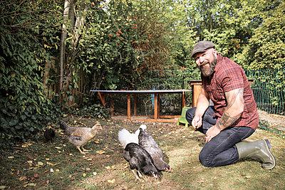 Man in his own garden, man feeding free range chickens - p300m2059307 von realitybites