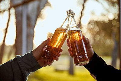 Hands of two male friends toasting with beer bottles - p300m2264400 by Aitor Carrera Porté