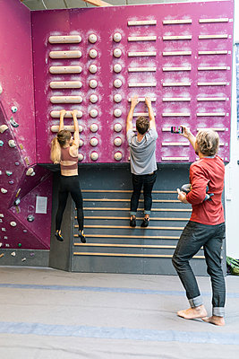 Male and female students practicing wall climbing while mature coach photographing in gym - p426m2170613 by Kentaroo Tryman