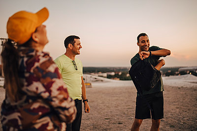 Happy male and female athletes standing on land during sunset - p426m2270866 by Maskot