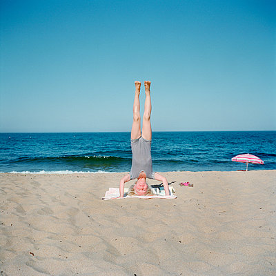 Girl doing handstand on beach - p528m1075428f by Johan Willner