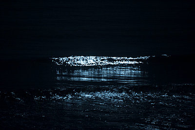 Moonlight reflecting on ocean waves at night - p624m1045686f by Odilon Dimier