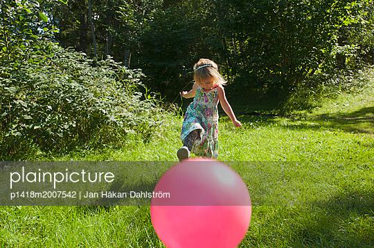 Kleines Mädchen kickt mit einem rotem Ball - p1418m2007542 von Jan Håkan Dahlström