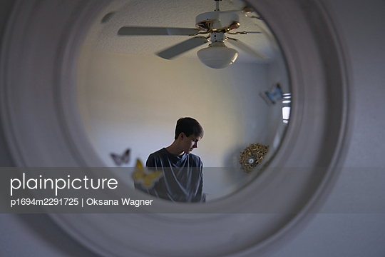 Reflection of contemplative young man in a mirror - p1694m2291725 by Oksana Wagner