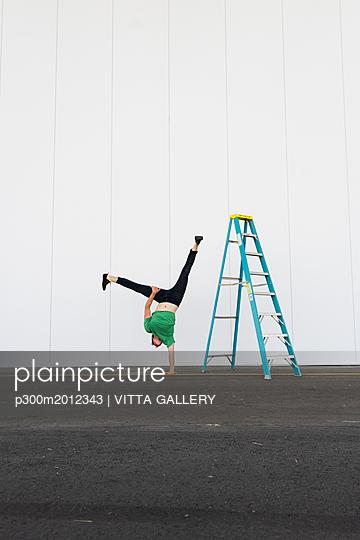 Acrobat training one-armed handstand next to ladder - p300m2012343 von VITTA GALLERY