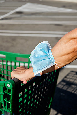 Man pushing a shopping cart with his face mask in his hand - p1423m2210962 by JUAN MOYANO