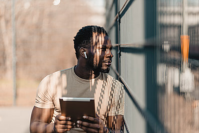 Young man looking away while holding digital tablet during sunny day - p300m2277067 by Gustafsson