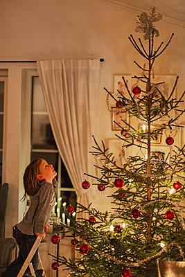 Girl looking at Christmas tree - p312m2092032 by Lisa  Öberg