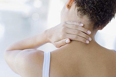 Woman rubbing sore neck - p6416725f by Sam Edwards
