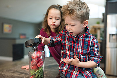 Little girl watching brother cover blender filled with beets and vegetable - p924m2074153 by Viara Mileva