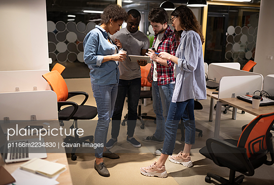 Diverse colleagues using tablet in modern workplace - p1166m2234830 by Cavan Images