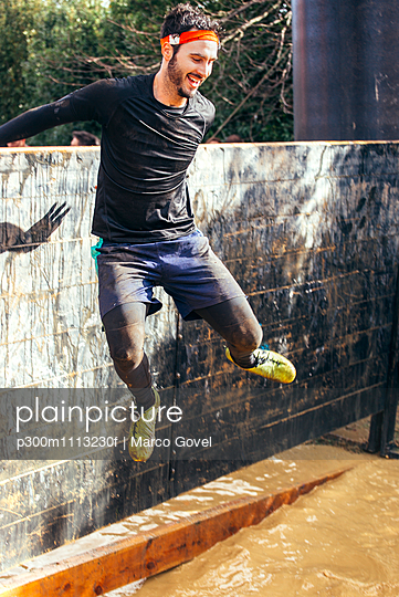 Participant in extreme obstacle race jumping over wall