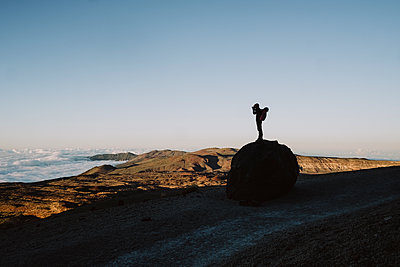 Silhouette of a male hiker taking photo of volcanic landscape - p1166m2124317 by Cavan Images