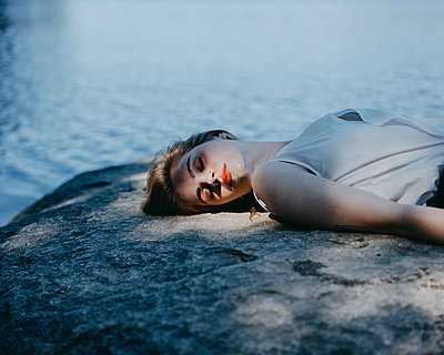 Young woman sleeping on the waterfront - p1184m1462615 by brabanski