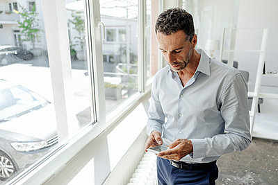 Businessman in office at the window looking at cell phone - p300m1499326 by Kniel Synnatzschke