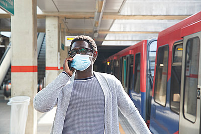 Male entrepreneur wearing protective face mask while talking on mobile phone at railroad station - p300m2241032 von Pete Muller