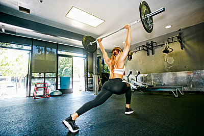 Mixed Race woman lifting barbell in gymnasium - p555m1304142 by Peathegee Inc