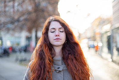 Young woman with closed eyes in the city - p975m2223813 by Hayden Verry