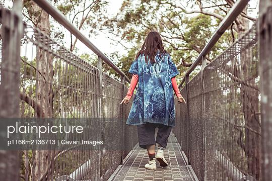 androgynous stylish figure runs fingers along railing on tree top walk - p1166m2136713 by Cavan Images