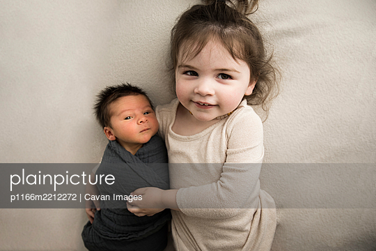 Big Sister Hugs Newborn Baby Brother While Laying on White Blanket - p1166m2212272 by Cavan Images