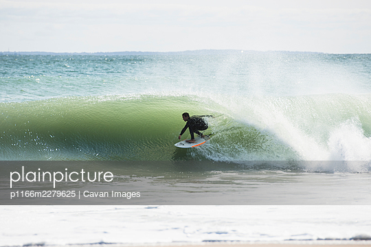Athletic Young Asian Man barreled in big summer hurricane waves - p1166m2279625 by Cavan Images