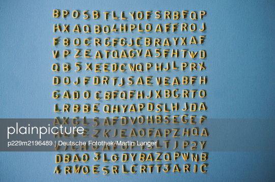 Yellow letters arranged on blue wall - p229m2196489 by Martin Langer
