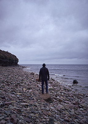 Mann steht auf Stein am Strand - p1124m1193530 von Willing-Holtz