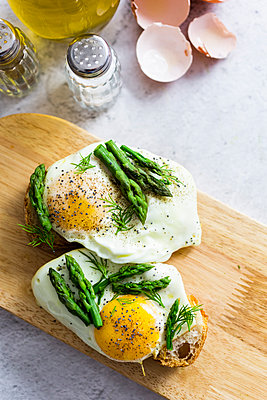 Slices of baguette garnished with fried eggs and Asparagus on a plate - p300m2114250 by Giorgio Fochesato
