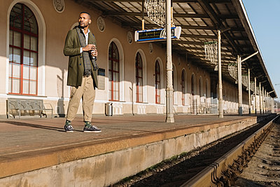 Stylish man with reusable cup waiting for the train - p300m2155303 by Hernandez and Sorokina