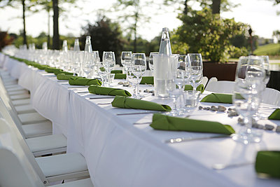 Festive laid table with green napkins and wine glasses - p300m911309f by Jan Tepass